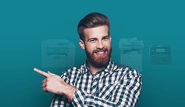 Homme souriant pointant du doigt des imprimantes Brother dans le fond