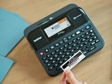 Imprimante d'étiquettes Brother P-touch D600 avec étiquette tenue à la main