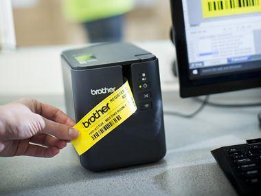 Imprimante d'étiquettes Brother P-touch P900W avec une étiquette jaune imprimée à partir d'un PC