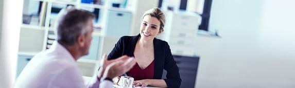 Réunion de travail : une femme en tailleur noir assise et discutant avec un homme en chemise mauve, une imprimante Brother en fond.