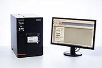 Imprimante d'étiquettes industrielles TJ à côté d'un écran d'ordinateur
