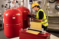 Ingénieur portant un casque jaune et une veste haute visibilité à genoux et prenant des notes, avec le scanner de documents portable DSmobile DS-940DW de Brother dans la salle des machines