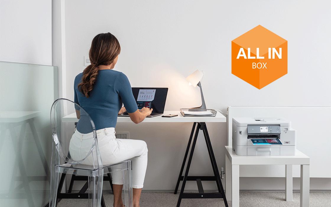 Femme assise à son bureau en télétravail avec le logo All in Box incrusté au dessus de l'imprimante