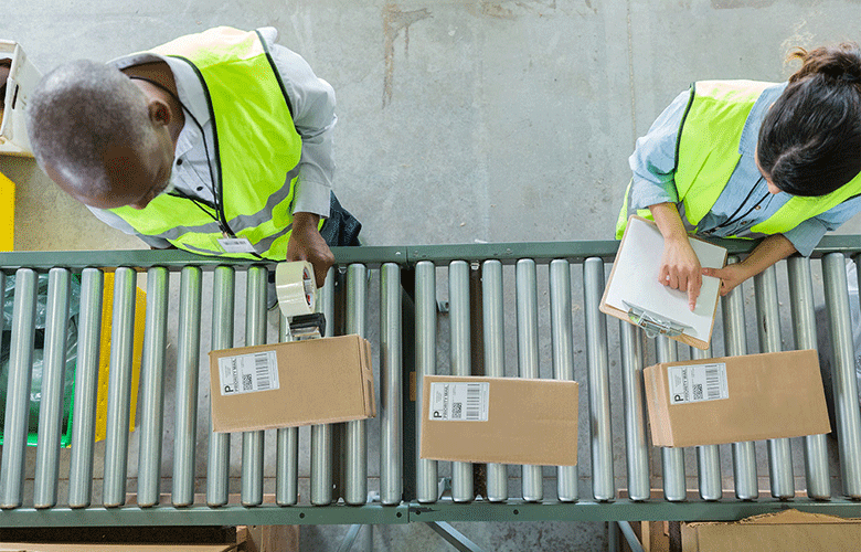 Man with tape gun standing over boxes on assembly line with woman holding clipboard in high vis vests