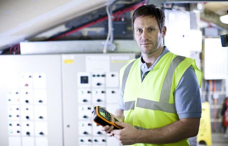 Electricien devant un tableau de distribution, tenant une imprimante d'étiquettes Brother P-touch