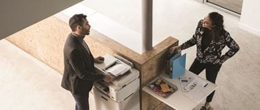 A man and a woman stop in a brightly lit office to talk by a business printer and some files