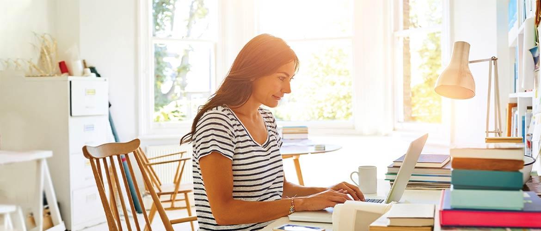 donna seduta alla scrivania davanti al pc lavora da casa