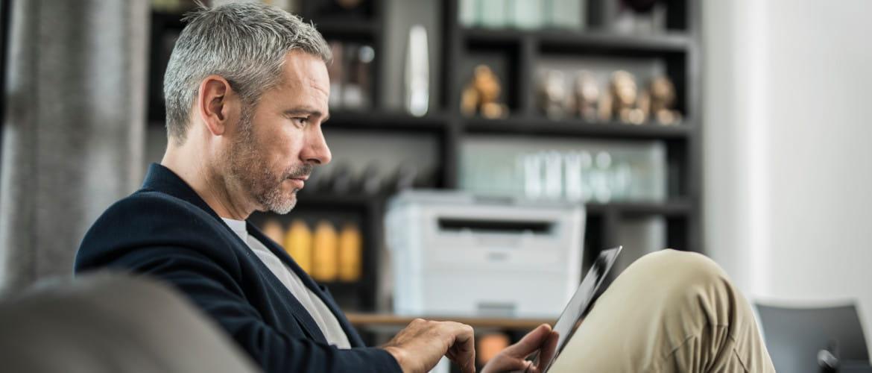 uomo lavora a casa in smartworking con una stampante Brother