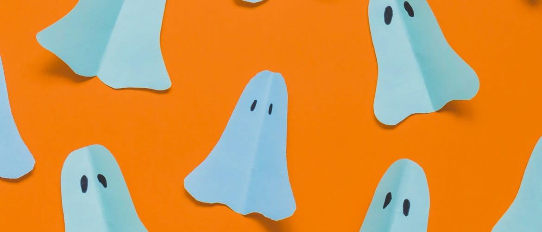 Piccoli fantasmi di carta su sfondo arancione