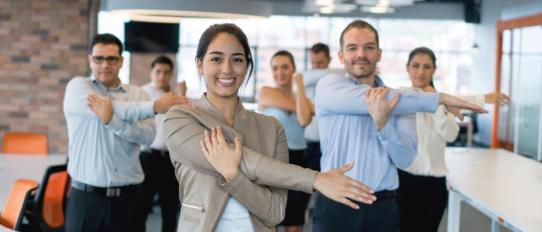 colleghi fanno esercizi di stretching posturali in ufficio