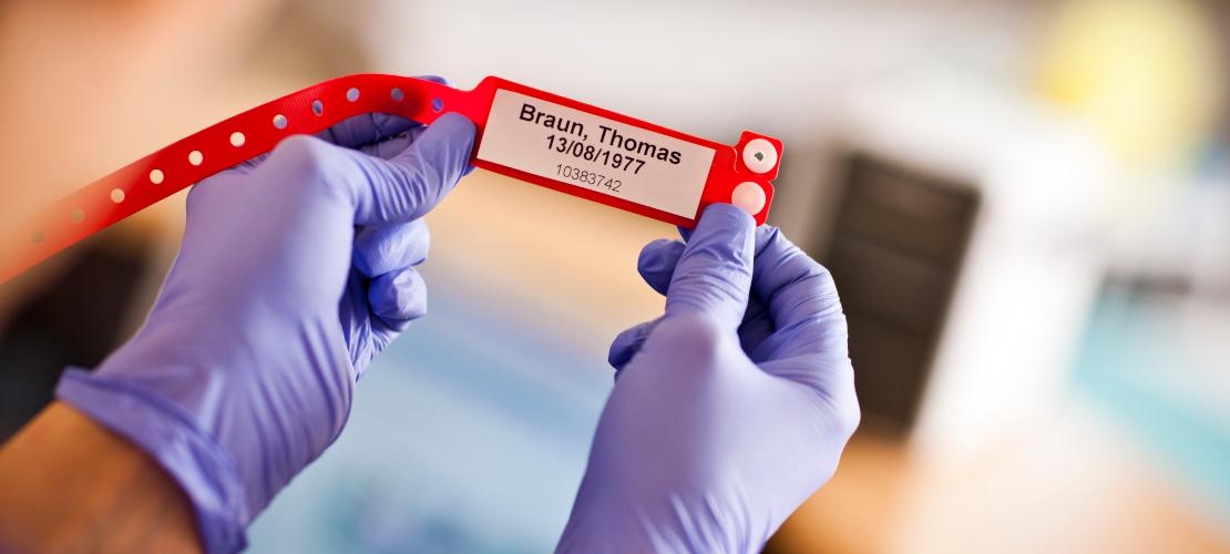 infermiere tiene in mano un braccialetto rosso identificativo