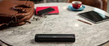 Stampante Brother PJ dentro una borsa, sopra un tavolo con agenda e caffè
