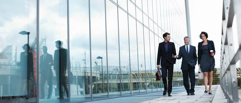Edifico moderno con vetrate e colleghi che camminano verso l'entrata