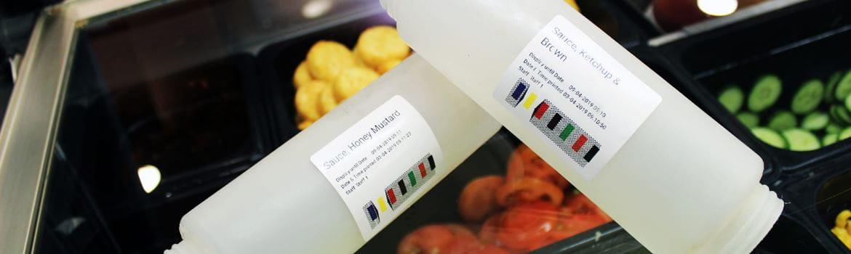 Due contenitori di salse etichettati con vassoi di insalata sullo sfondo