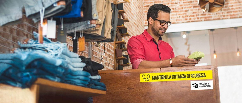 Commesso in un negozio di abbigliamento accetta pagamenti contactess