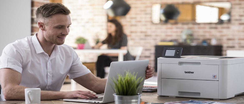 Ragazzo scrive al portatile con a fianco una stampante laser Brother A4
