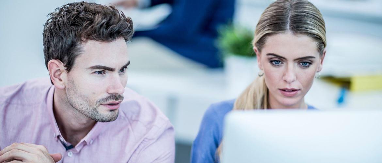 donna e uomo che guardano lo schermo del pc in ufficio