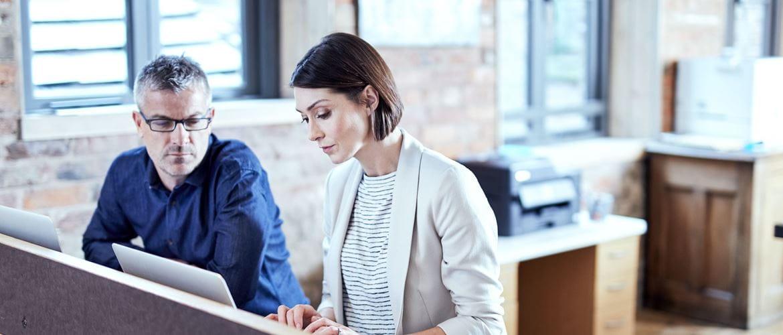 Impiegata seduta alla scrivania scrive al PC portatile mentre un suo collega osserva