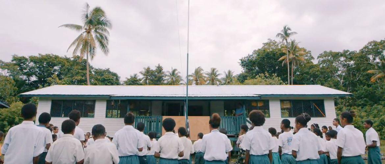 Ragazzi voltati di spalle di fronte a una scuola nella foresta pluviale