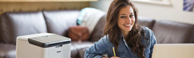Ragazza sorridente con una stampante laser HL-1210W nella sua casa