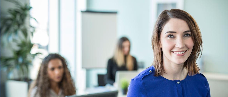 donna sorridente in ufficio. Sullo sfondo due colleghe che lavorano sedute alla scrivania