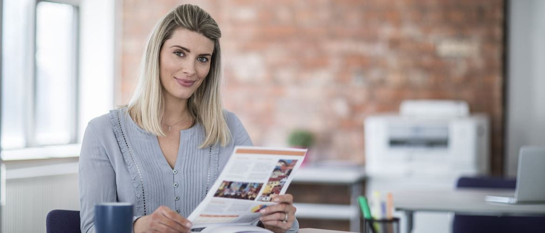 Impiegata bionda sorridente in ufficio con in mano un foglio a colori stampato con stampante inkjet Brother