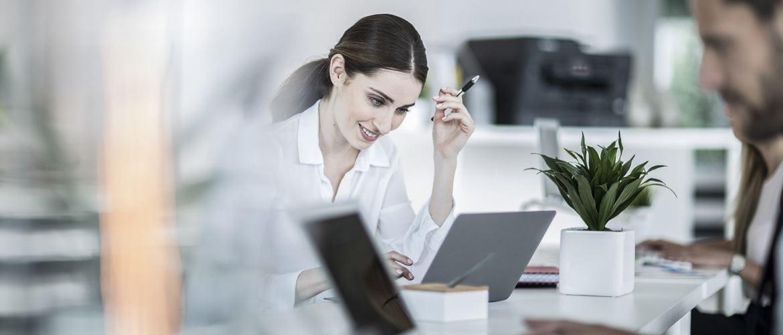 Ragazza sorridente al lavoro con il suo laptop