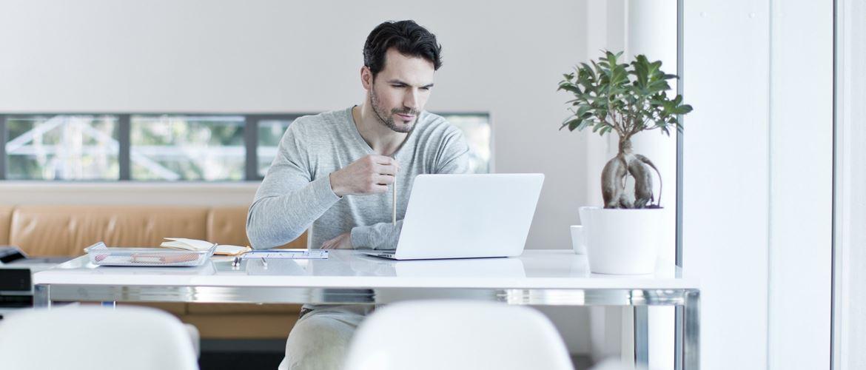 Ragazzo con maglietta grigia al lavoro al suo PC portatile in un ufficio moderno