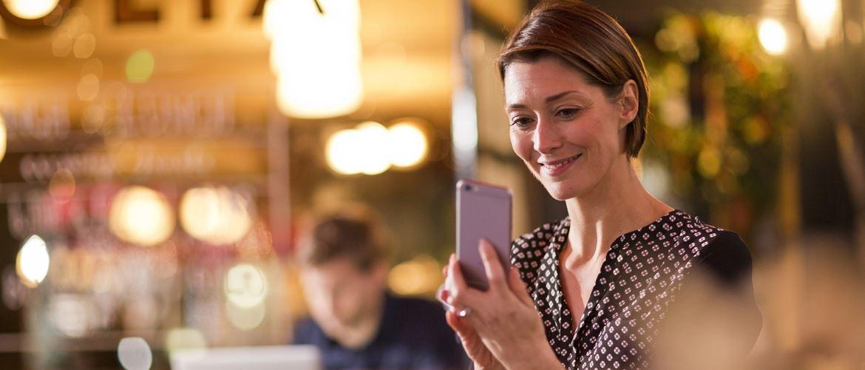 Ragazza sorridente guarda il suo smartphone in un negozio