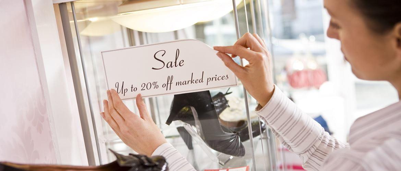 Impiegata in un punto vendita di scarpa attacca un'etichetta che evidenzia lo sconto sui prodotti in vendita