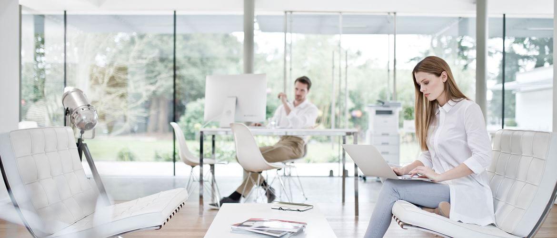 Ragazza e ragazzo al lavoro in un ufficio openspace con stampante multifunzione laser Brother