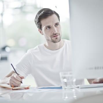 Ragazzo al lavoro al PC mentre prende appunti