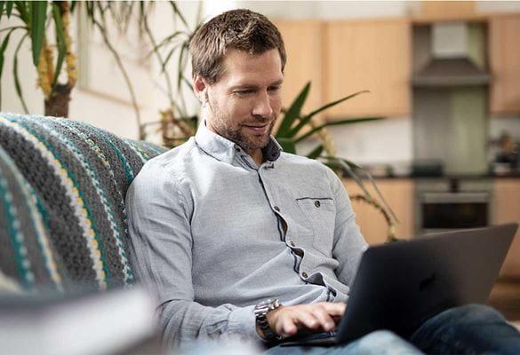uomo seduto sul divano con laptop lavora da casa