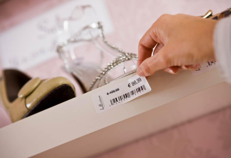 commessa mette l'etichetta con il prezzo sullo scaffale