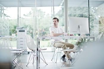 Ragazzo in un open space al lavoro al PC collegato wireless con la stampante multifunzione laser mono MFC-L6900DWT