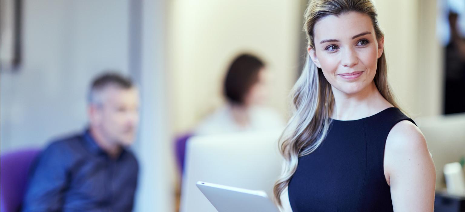 Ragazza sorridente in ufficio con tablet in mano. Colleghi sullo sfondo