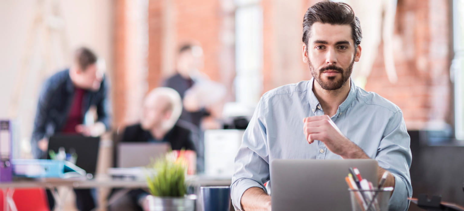 Ragazzo seduto alla scrivania davanti al laptop con collegi alle spalle