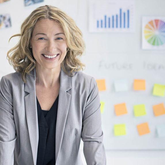donna sorridente in ufficio con post-it colorati sulla parete