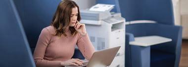 Donna seduta vicino al multifunzione Brother MFC-L6900DW in un ufficio