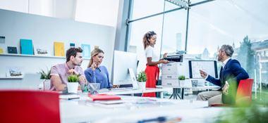 colleghi in ufficio alla scrivania, donna in piedi alla stampante
