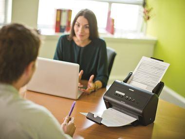 Impiegati al lavoro in ufficio con scanner desktop Brother ADS-3000N