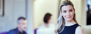 Ragazza bionda sorridente in ufficio con colleghi sullo sfondo
