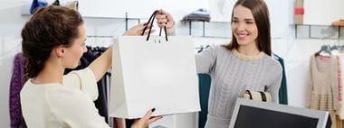 Ragazza sorridente riceve la sua borsa con gli acquisti dalla cassiera all'intero di un negozio retail