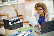 Ragazza al lavoro nel suo ufficio in casa con foglio stampato da stampante multifunzione laser Brother DCP1612W
