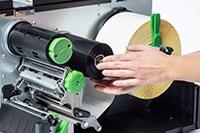 Nastro termico arrotolato all'interno della stampante industriale per etichette