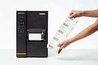Rotolo di etichette prestampato accanto alla stampante industriale per etichette TJ