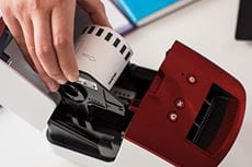 Donna carica un rotolo di etichette DK nella stampante Brother QL-600R