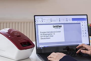 Brother QL-600B stampante di etichette accanto a un portatile
