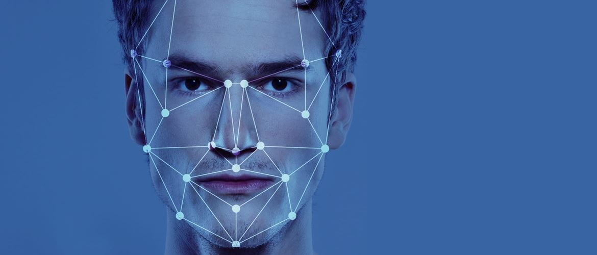 Facial recognition graphical outline superimposed onto a young man's face over a blue background