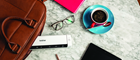 A flatlay of a white Brother portable mobile scanner, turquoise coffee cup and saucer, black ipad, bright pink notebook, brown leather laptop bag, a pair of glasses, a  pencil on top of a marble effect table background